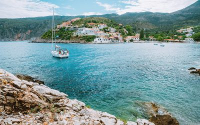 Assos cute town, on Kefalonia island, Greece. View of beautiful bay with sail yacht boat and mountains in background