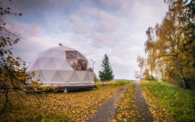 Large geodesic dome tent in autumn forest. Modern outdoor glamping tent on meadow.