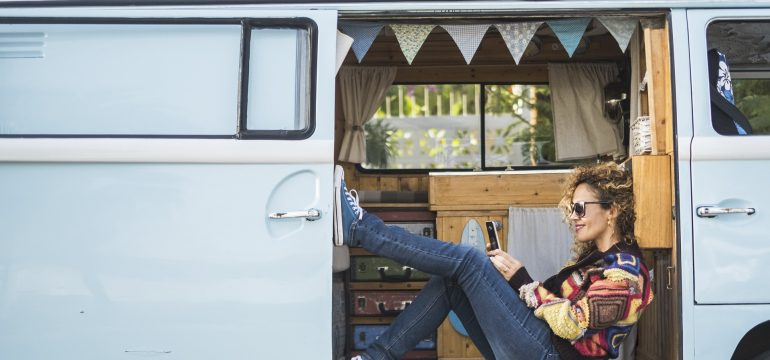 Alternative lifestyle and little cozy home beautiful vintage blue van - happy caucasian woman use technology inside a legendary camper during van life or vacation - wanderlust and phone internet